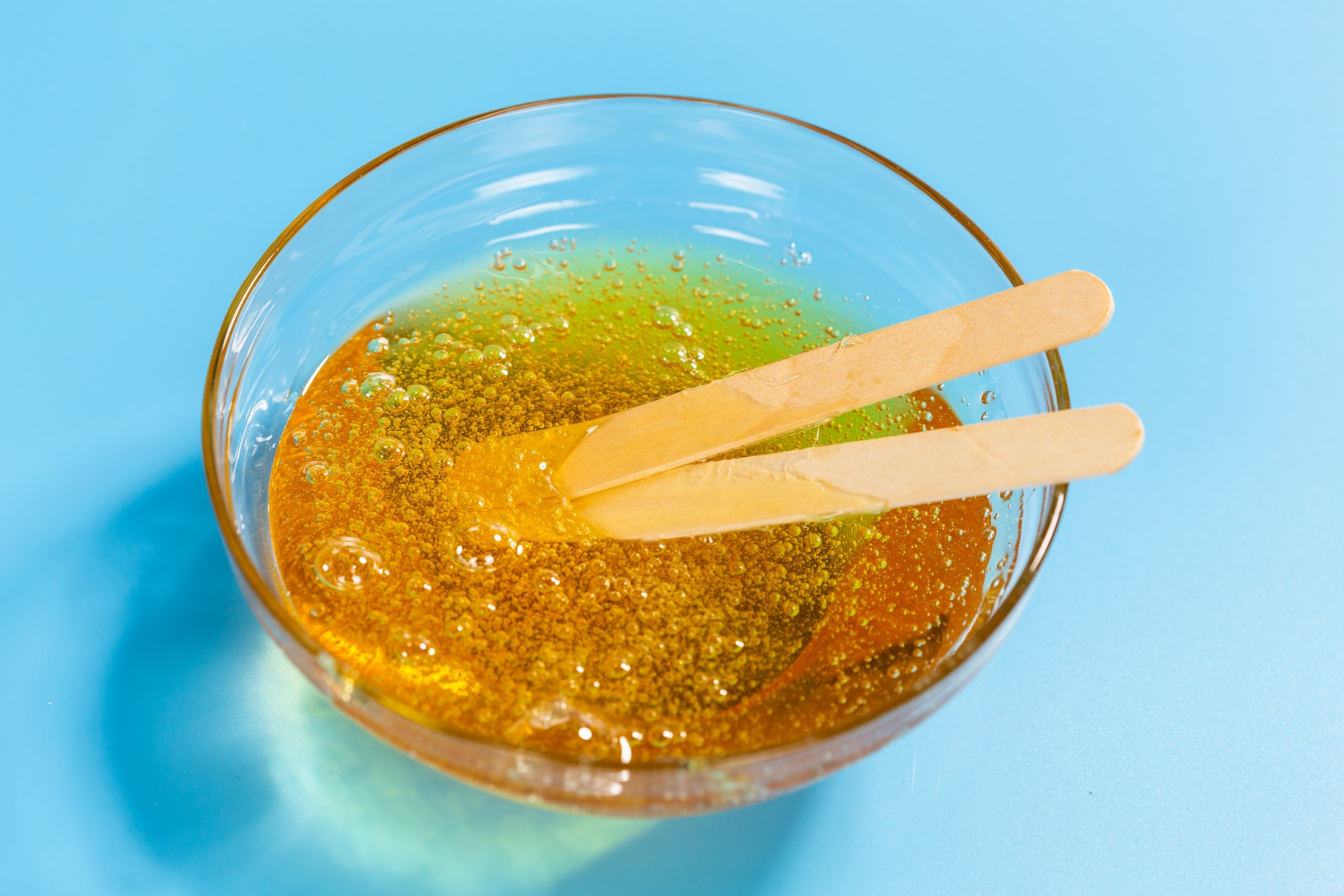 Depilation and beauty concept - close-up of sugar paste or honey wax for hair removing spatula with