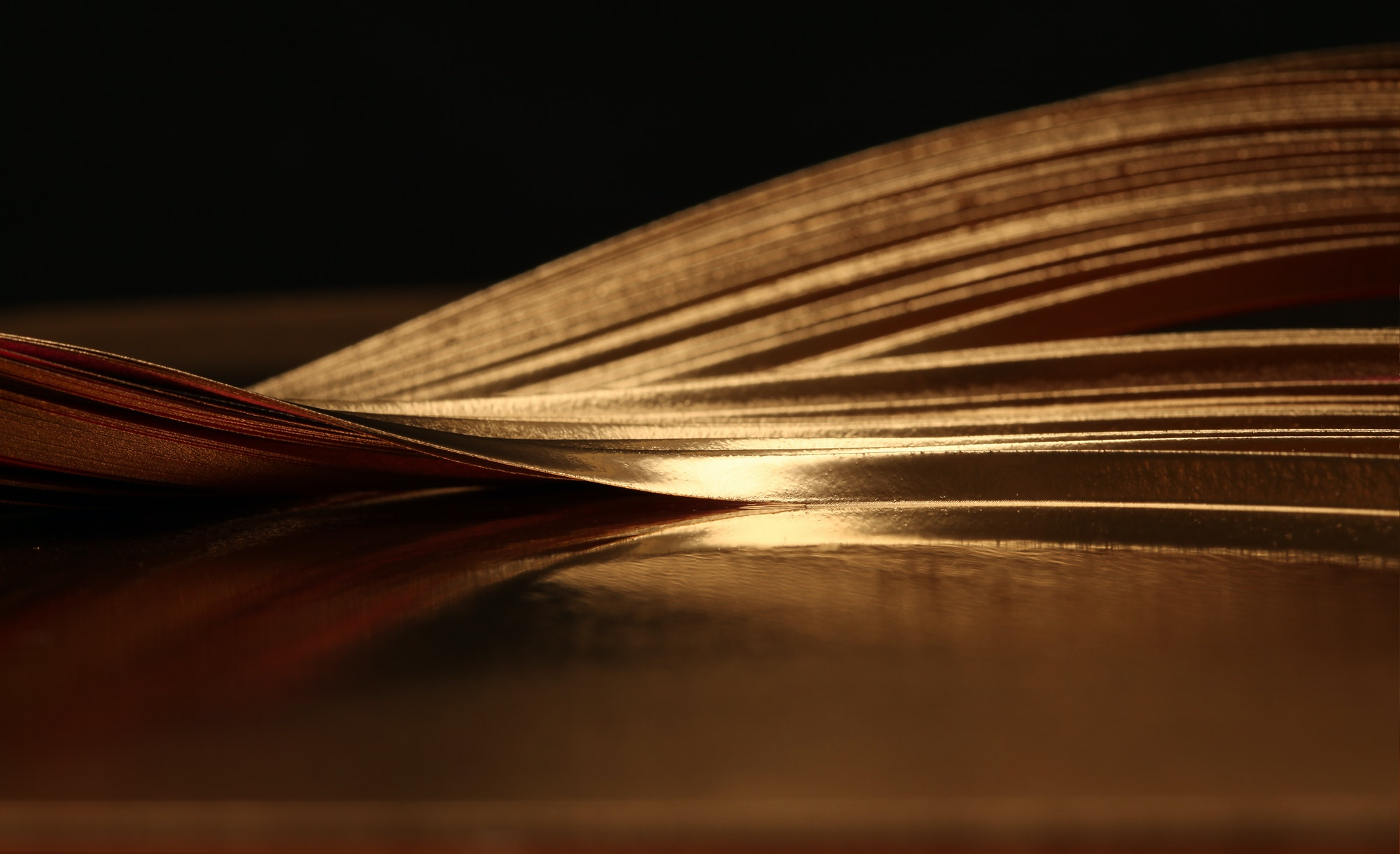 Soft focus Abstract background. Gold (bronze) paper wave on black.